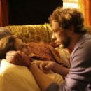 Lia (Lisa Ray) and Jack (Kristen Holden-Ried) at couch.