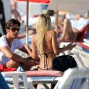 Shauna Sand puts on a pair of tiny pink shorts as she gathers her things and leaves the beach with her husband, Laurent Homburger - 454 x 338