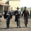 Evil rancher Denton Baxter (Michael Gambon, center), flanked by his henchmen, arrives at Harmonville's Main Street for a decisive gun battle.