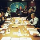 Director Oliver Stone (standing, center) on the set of his film W., with (left to right, seated) Condi Rice (Thandie Newton), Donald Rumsfeld (Scott Glenn), George Tenet (Bruce McGill), George W. Bush (Josh Brolin, seated on table), Colin Powell (Jeffrey