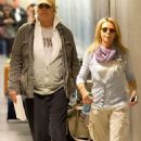 Heavy cargo coming through: Chevy Chase has excess baggage as he wheels both his and wife's luggage through airport - 454 x 664