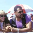 Queenie (Lisa Bonet) and Smoke (Laurence Fishburne) watch a race from the sidelines