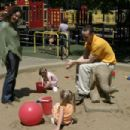 Susan (Melanie Lynskey) and Paul (Peter Paige) playing with children in the park in a scene from SAY UNCLE - 454 x 302