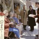 Longfellow Deeds (Adam Sandler, right) delivers pizza as Cedar (Peter Gallagher, center right) and his crony, Anderson (Erick Avari, center left) look on in Columbia's Mr. Deeds - 2002