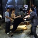 Jennifer Love Hewitt get some help from Jackie Chan on one of her high-kicking moves, as director Kevin Donovan (rear center) and star Ritchie Coster (rear right) watch in Dreamworks' The Tuxedo - 2002