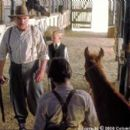 Boss Man (Jan Decleir, left) and his son (Nicholas Trueb, center) confront Richard (Chase Moore, foreground) after they learn he has stolen medicine from Boss Man's prized stallion, Caesar, to help Lucky (voiced by Lukas Haas) in Columbia's Runnin - 400 x 267