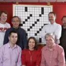 L-R standing: Current crossword champion Tyler Hinman, past multiple-year champion Jon Delfin, NY Times Crossword editor Will Shortz, master crossword constructor Merl Reagle.  L-R sitting: past multiple-year champion Trip Payne, one-time champion Ellen R
