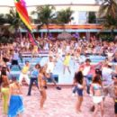 A large group of partygoers – including Kelly (Kelly Clarkson, in blue top) and Justin (Justin Guarini, in coral shirt and white T-shirt) – celebrate Spring Break, in song and dance.
