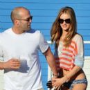 Jason Statham and Rosie Huntington-Whiteley hold hands as they leave the beach in Miami. Rosie could be seen sporting an American Flag belly shirt and bikini bottoms while Jason carried what looked like a cup of beer. **UK, GERMANY, SCANDINAVIA & AUSTRALI