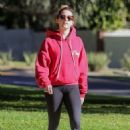 Ashley Tisdale in a red hoodie and black leggings for a walk in Los Feliz