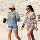 Cindy Crawford, Stacy Keibler, and some girl friends carry beverages with them as they stroll along the beach together
