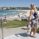 Paris Hilton wears a cutout blue one-piece bathing suit as she poses for photographs at Bondi Beach