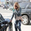 Ashley Tisdale fills up at the gas station in Los Angeles while chatting on her phone December 7, 2012