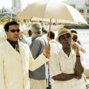 (left to right) Russell Hornsby as 'Jean-Paul' holds the umbrella for his boss 'Moore' (Don Cheadle) in New Line's film AFTER THE SUNSET. © 2004 Glen Wilson/New Line - 454 x 363
