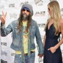 Rob Zombie and Sheri Moon Zombie attend the 2015 Journeys AP Music Awards, Fueled by Monster Energy Drink at Quicken Loans Arena on July 22, 2015 in Cleveland, Ohio. - 454 x 403