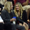 Vince Neil talks with makeup artist Rain Hannah during the Outlaws' game against the Los Angeles Kiss at the Thomas & Mack Center on May 4, 2015 in Las Vegas, Nevada.