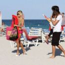 Shauna Sand puts on a pair of tiny pink shorts as she gathers her things and leaves the beach with her husband, Laurent Homburger