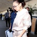 Bella Hadid – Arriving at LAX in a light pink jump suit - 454 x 825