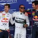 Pole sitter Lewis Hamilton (C) of Great Britain and Mercedes GP celebrates in parc ferme with second placed Sebastian Vettel (L) of Germany and Infiniti Red Bull Racing and third placed Ma