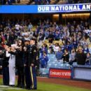 Gene Simmons sings the National Anthem before the game between the Atlanta Braves and the Los Angeles Dodgers at Dodger Stadium on May 08, 2019 in Los Angeles, California - 454 x 317