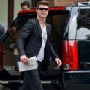 Robin Thicke waves to fans as he steps out of a building in downtown Manhattan
