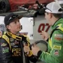 Kimi Raikkonen, left, of Finland, talks with Kyle Busch, right, during practice for the NASCAR truck series North Carolina Lottery 200 auto race in Concord, N.C., Friday, May 20, 2011. (AP Photo/Terry Renna)
