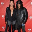 Musician Slash (R) and Perla Hudson attend the MusiCares MAP Fund Benefit Concert at Club Nokia on May 12, 2014 in Los Angeles, California - 398 x 594