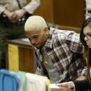Chris Brown appears in court with his lawyer Setara Qassim for a probation progress hearing in Los Angeles Superior Court on August 13, 2014 in Los Angeles, California