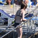 Lily Collins in Black Bikini at the beach in Ischia