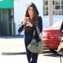 Khloe Kardashian, wearing a navy blue sweat suit, is spotted grabbing a cup of coffee at a Starbucks before entering an office building in Los Angeles
