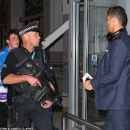 Cristiano Ronaldo comes face to face with a stern-looking armed policeman at Manchester Airport