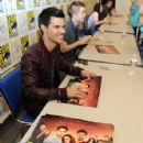 Taylor Lautner, Robert Pattinson, and Kristen Stewart sign posters for fans at The Twilight Saga: Breaking Dawn - Part 1 Comic-Con Fan Meet and Greet on July 21, 2011 in San Diego, California