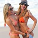 Leann Rimes in an Apricot bikini and her friend romp together in the surf in Hawaii