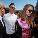 Smile for the camera! Cara Delevingne gets into the Grand Prix spirit as she dons plunging racer jumpsuit and metallic shades while hanging out with Cristiano Ronaldo