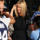 """Jennifer Aniston poses for pictures and signs autographs in a little black dress ahead of an appearance on """"The Daily Show with Jon Stewart."""" The actress, who is currently rumoured to be engaged to actor Justin Theroux, wears a diamond ring on her right h"""