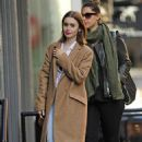 Lily Collins crossed paths with a girlfriend in SoHo today (October 18)