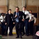 Oliver Porter (LEWIS BLACK, center) orders Zach Van Bourke, (WILMER VALDERRAMA, left) security guard Hoffman (ROB RIGGLE, right) and others to chase after the unaccompanied minors in Warner Bros. Pictures' and Village Roadshow Pictures' comedy - 454 x 301