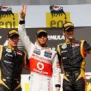 First placed Lewis Hamilton (C) of Great Britain and McLaren celebrates on the podium with second placed Kimi Raikkonen (L) of Finland and Lotus and third placed Romain Grosjean (R) of France and Lotus following the Hungarian Formula One Grand Prix at the