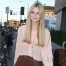 Mischa Barton, wearing high waisted brown shorts and a peach colored top, is followed by a camera crew as she strolls along Robertson Blvd
