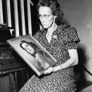 Mrs. Florence Spangler, listening to radio as she holds photo of her missing daughter, Jean Elizabeth Spangler.