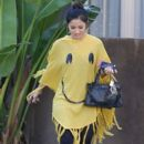 Brenda Song covers up in a yellow smiley face poncho as she goes on a coffee run in Los Angeles