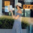 Ashley Greene – Reads a book while waiting in line at the grocery store in Beverly Hills