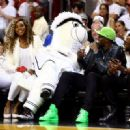 Tennis player Serena Williams (L) and runner Usain Bolt (R) attend Game Four of the 2014 NBA Finals between the Miami Heat and the San Antonio Spurs at American Airlines Arena on June 12, 2014 in Miami, Florida. NOTE TO USER: User expressly acknowledges a - 454 x 329