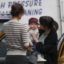 Helena Christensen putting her child into a waiting taxi in New York City - February 17, 2011