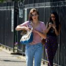 Milla Jovovich checks a paper as she rushes to an appointment in downtown New York