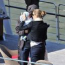 Gisele Bundchen carries her 4-month-old son Benjamin as she and husband Tom Brady disembark a yacht on the river Seine in Paris