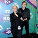 Singer Billy Idoland iHeartMedia radio personality Mark Wallengren pose backstage during the first ever iHeart80s Party at The Forum on February 20, 2016 in Inglewood, California. - 406 x 600