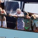 Queen's Roger Taylor uses a pole and shoots an AIRGUN at jellyfish whilst on a boat ride with his wife and children during sun-soaked holiday in Spain, 31 May 2019 - 454 x 296